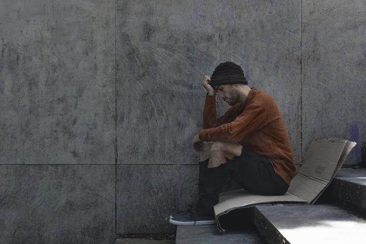 Muž bez domova sedí na ulici