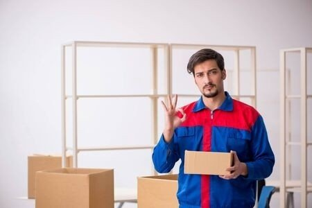 Muž s balky ve skladu ukazuje symbol OK