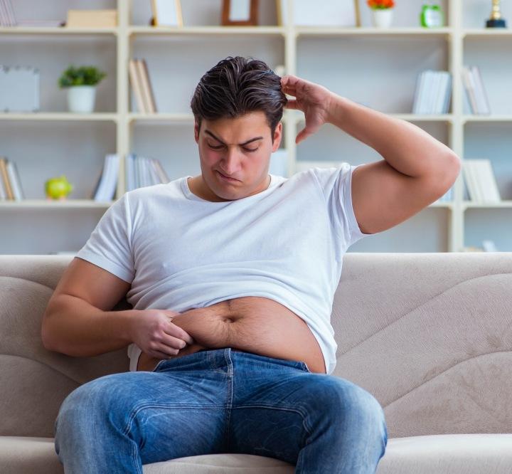 Muž s nadváhou sedí na gauči.