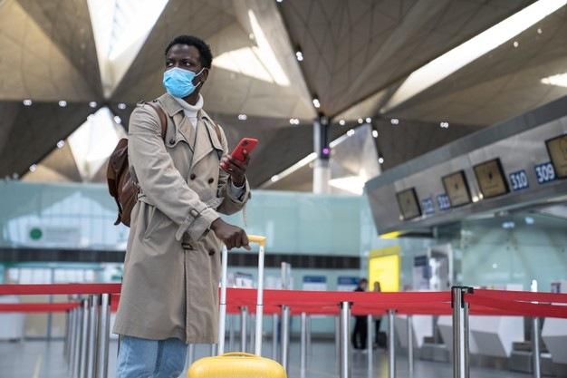 Muž s rouškou na letišti.