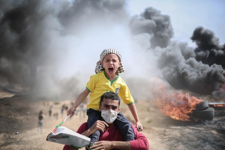 Muž nese syna uprostřed bombardování.
