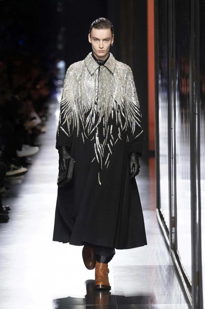 Muž v černém kabátu Dior se třpytivým efektem