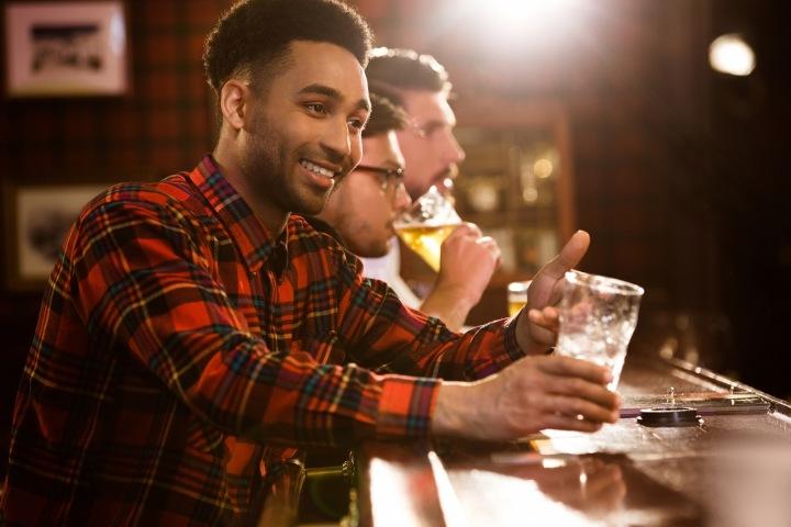 Muž v kostkované košili sedí u baru a pije pivo