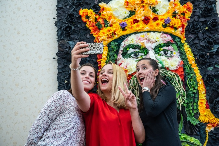 Tři kamarádky se fotí před malbou z květin