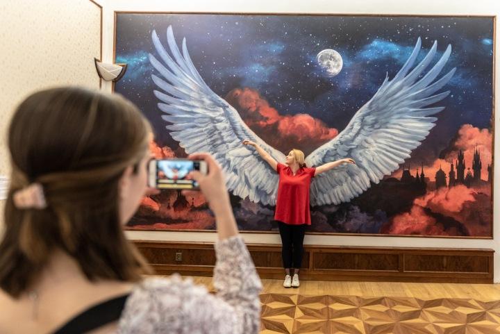 Dívka v muzeu se nechává fotit před obrazem s velkými křídly