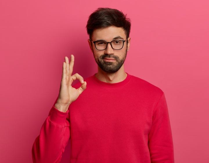 Na obrázku je muž v červeném svetru