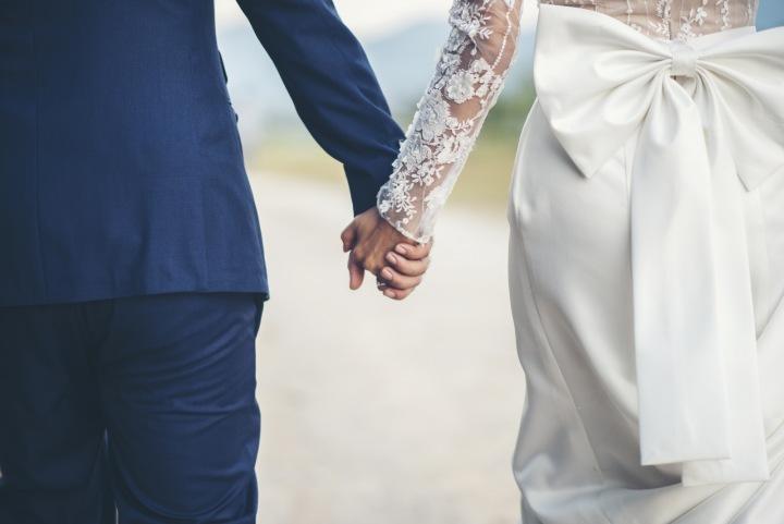 Novomanželé se drží na ruku.