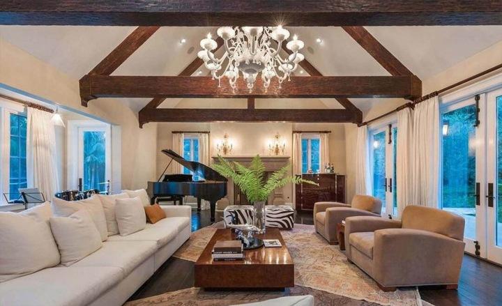 Obývací pokoj se světlými křesly a dřevěnými trámy pod stropem
