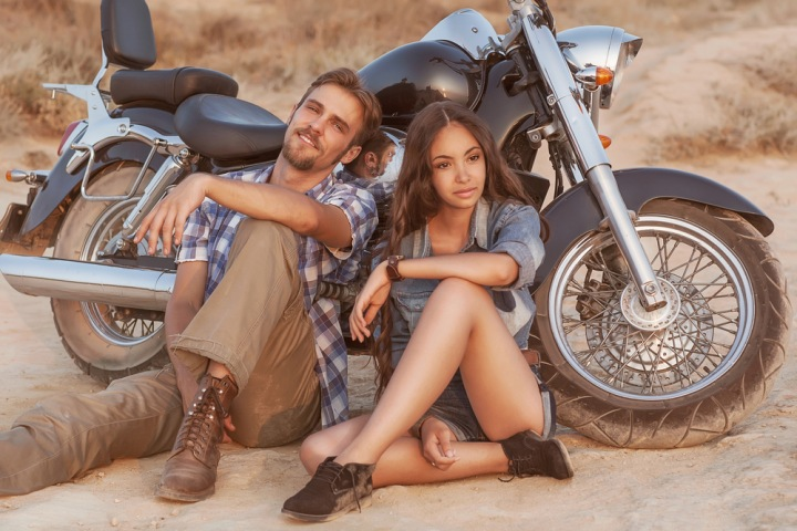 Žena s mužem odpočívají u motorky.