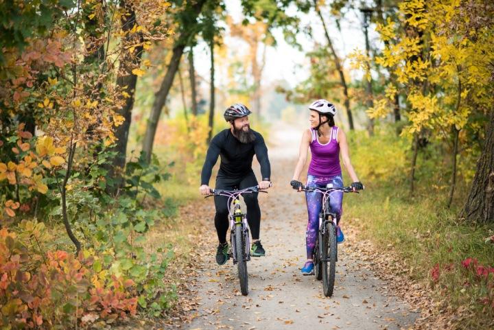 Pár jede na kole lesem.
