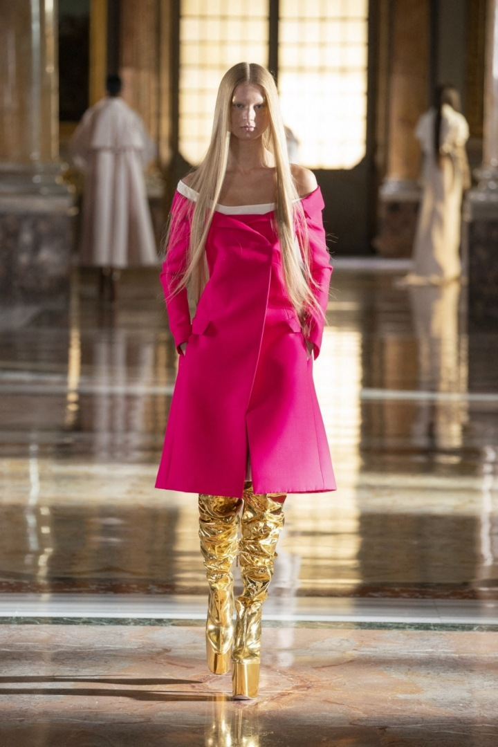 Modelka v růžovém kabátku a zlatými botami na platformě