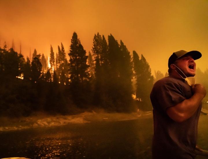 Na fotografii stojí křičící muž, v pozadí řádí požár