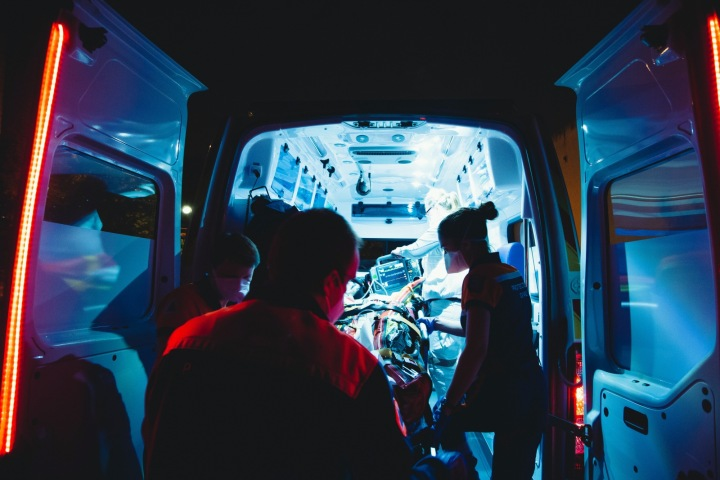 Zdravotníci nakládají pacienta do sanitky