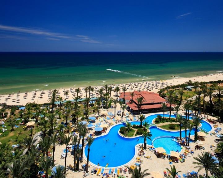 Hotelový komplex s bazeném a moře z ptačí perspektivy.