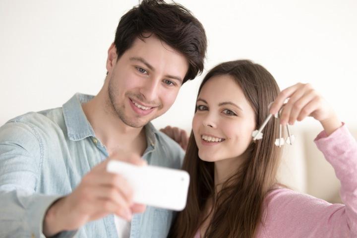 Mladý pár právě si dělá selfie s klíčem od nového bytu