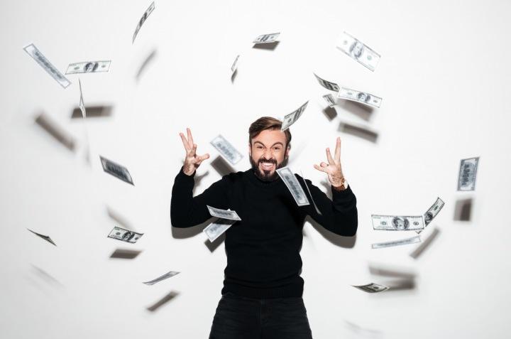Šťastný muž rozhazující kolem sebe bankovky