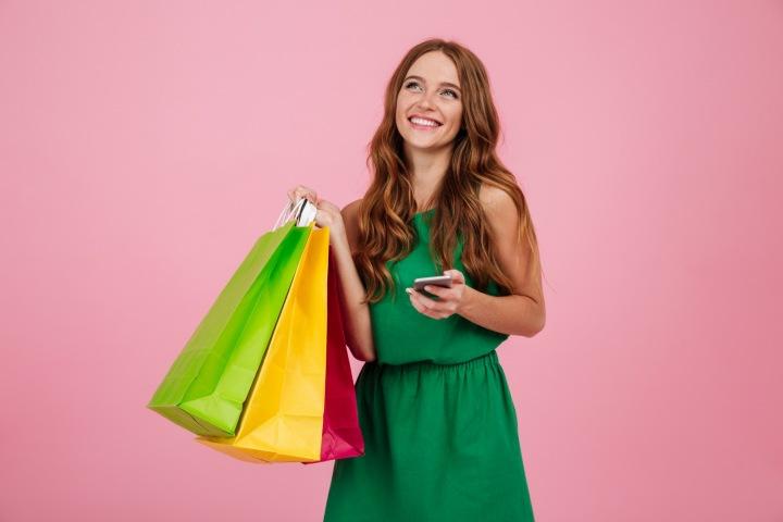 Spokojená a zadostiučiněná mladá dívka s nákupními taškami