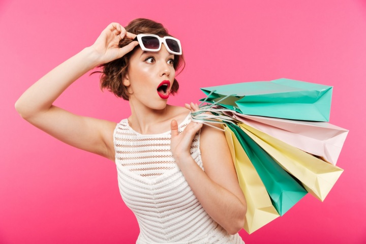 Mladá žena s nákupními taškami a slunečními brýlemi
