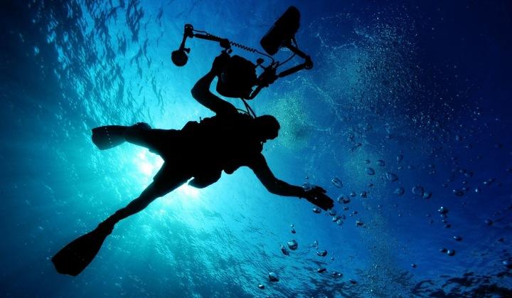 Potápěč, který plave pod vodou.