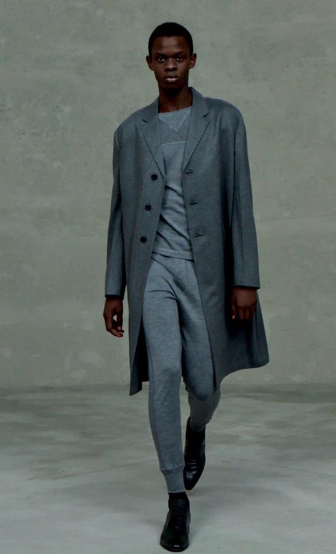 Muž v teplákách a šedém kabátu Prada