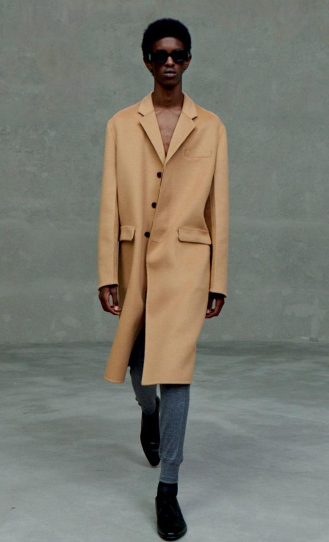 Muž v béžovém kabátu Prada