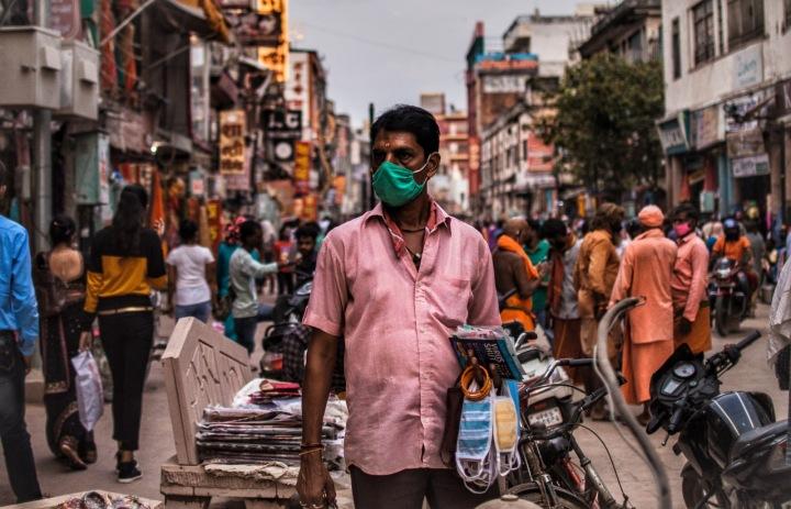 Prodavač roušek na trhu v indickém Váránasí