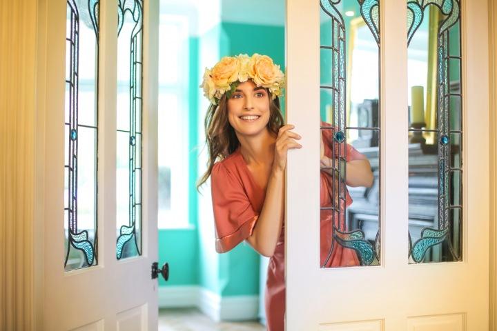 Krásná dívka s věnečkem na hlavě ve dveřích luxusní vily
