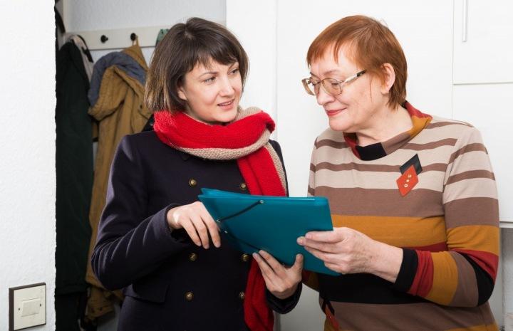Mladší žena pomáhá starší s dokumenty