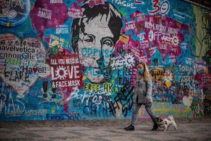 Dívka se psem procházející kolem Lennonovy zdi