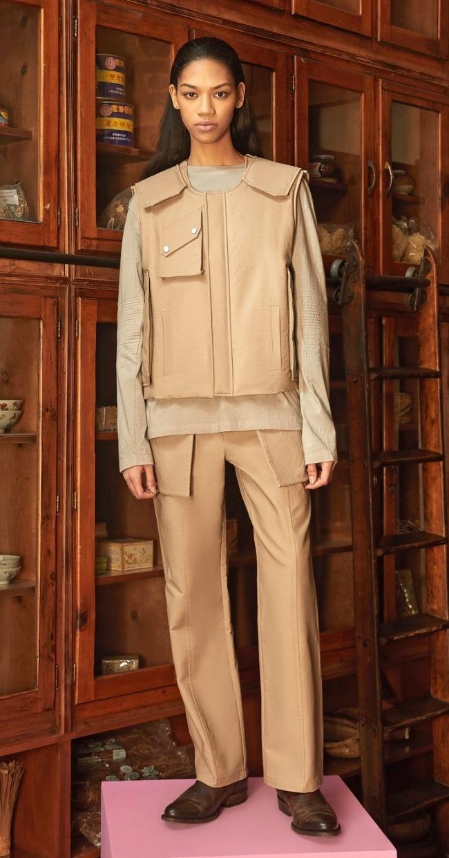 Modelka v bundě a kalhotách s velkými kapsami