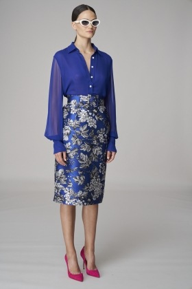 Žena v modré květované sukni a halence
