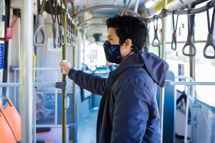 Muž v tramvaji s rouškou