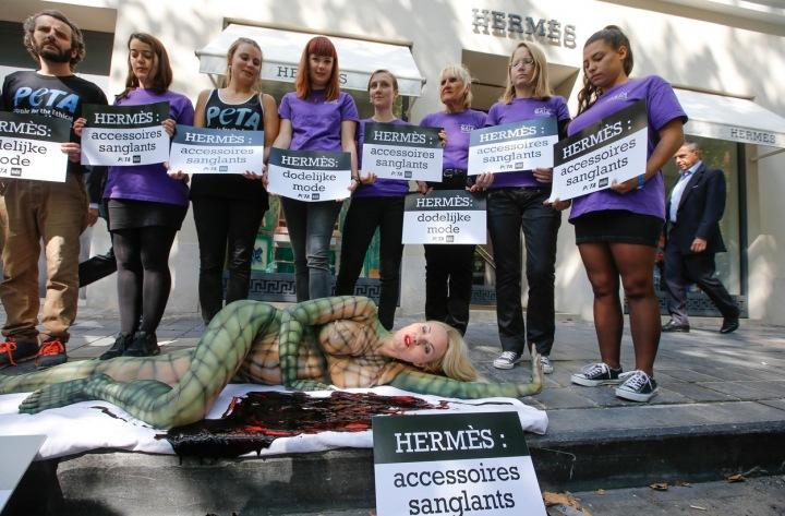 Skupina lidí stojí s plakáty za ženou pomalovanou jako plaz. Protest aktivistů PETA v Belgii v roce 2015.