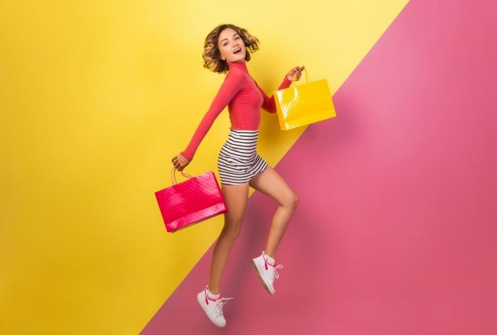 Veselá barevná dívka s taškami ve výskoku