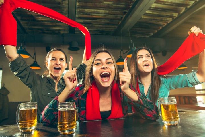Trojice fotbalových fanynek sleduje zápas v baru