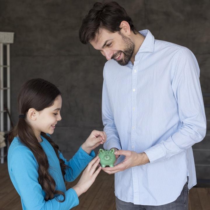 Otec s dcerou házejí drobné do prasátka.