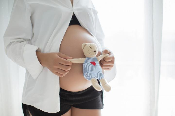 Těhotná žena s plyšákem.
