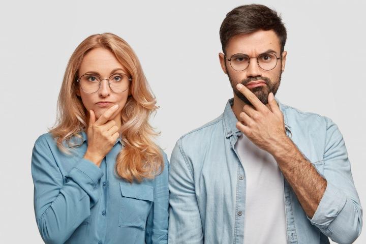 Přemýšlející pár mladých lidí v brýlích.