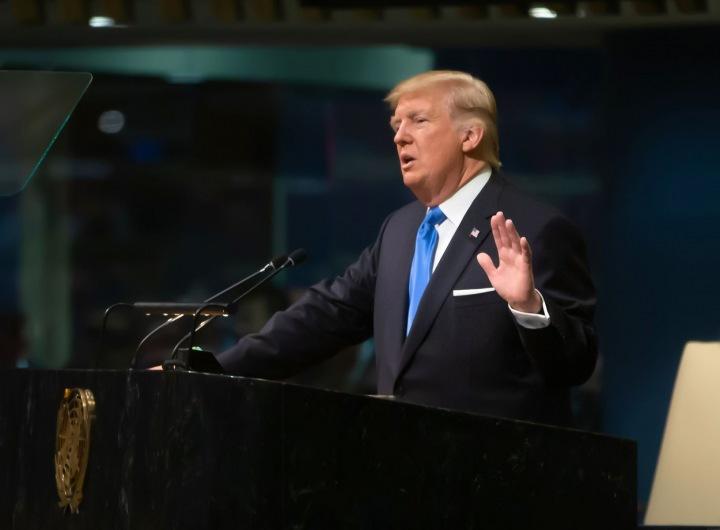 Trump stojí u řečnického pultu, na sobě má tmavý oblek a modrou kravatu.