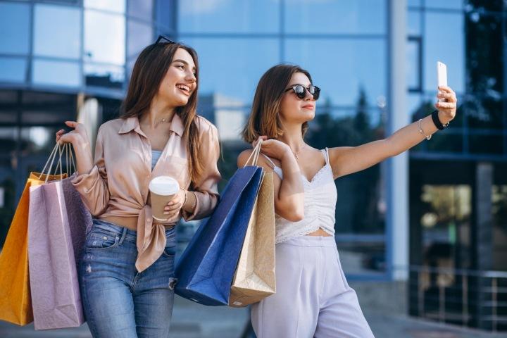 Kamarádky na nákupech s taškami, dělající si selfie