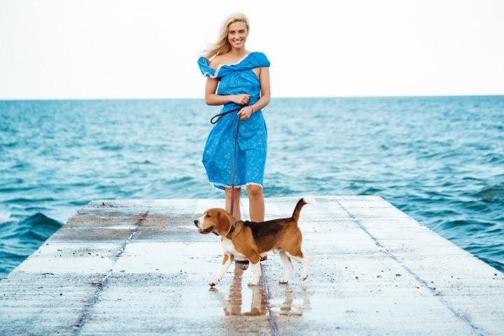 Dívka v modrých šatech u moře se psem