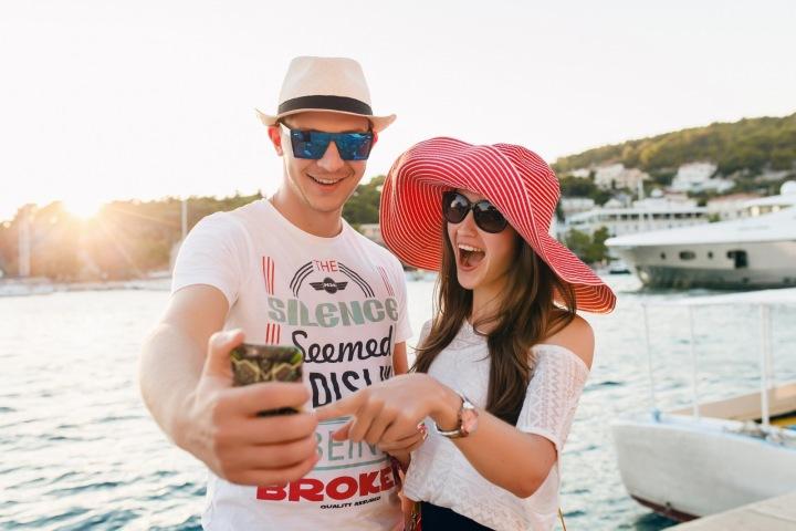 Pár užívající si dovolenou, usmívající se pro selfie