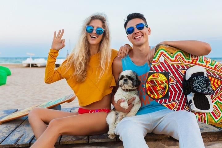 Baevný cool pár mladých lidí na surfařské dovolené se psem