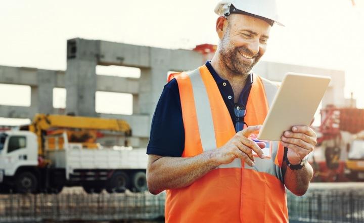 Zaměstnanec v oranžové reflexní vestě stojí na stavbě