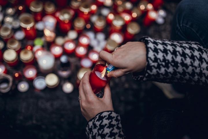 Ruce, co zapalují svíčku.