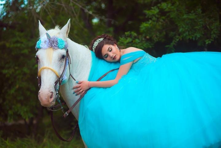Žena v modrých šatech na koni.