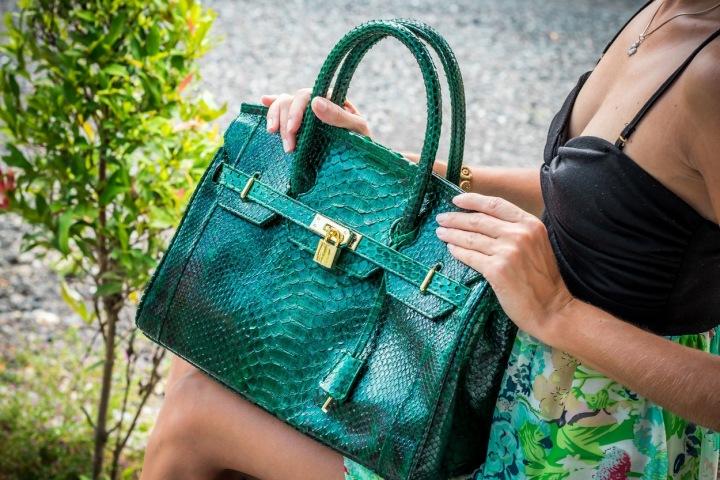 Žena drží zelenou kabelku z krokodýlí kůže