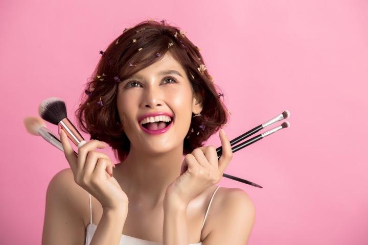 Žena drží několik kosmetických štětců a tváří se šťastně