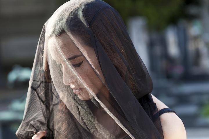 Žena v černém závoji na hřbitově