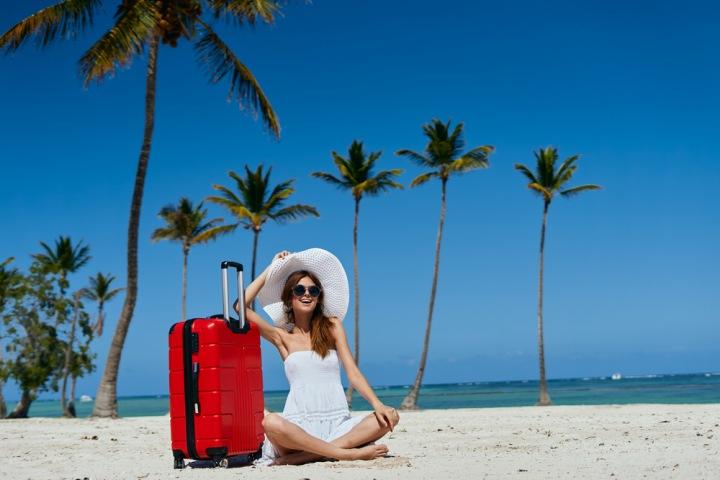 Žena na pláži s kufrem.